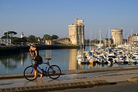 France, Charente Maritime, La Rochelle, cyclist in front of the old harbour with Tour de la Chaine on the left and Tour Saint Nicolas on the right