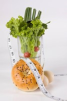 Tape measure around a glass full of vegetables with a bagel and brown eggs