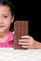 Portrait of a girl holding a bar of chocolate