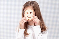 Close_up of a girl looking through a slice of bread