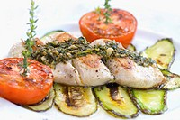 High angle view of grilled fish with zucchini and tomatoes