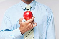 Mid section view of a businessman holding a red apple