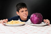 Boy choosing between a plate of French fries and a red cabbage