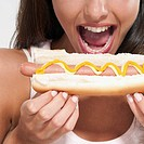 Close_up of a woman eating a hot dog