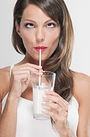 Woman drinking milk with a straw