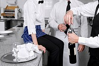 Waiter opening a wine bottle