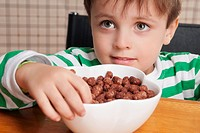 Close_up of a boy eating dry cereal