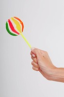 Close_up of a human's hand holding a lollipop