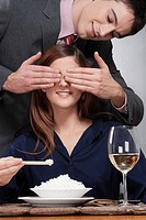 Woman eating rice and a man covering her eyes