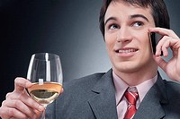 Businessman talking on a mobile phone and drinking wine