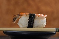 Close_up of a Nigiri Sushi with chopsticks on a bowl