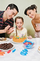 Girl celebrating her birthday with her parents