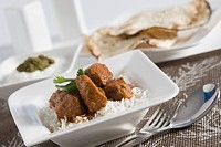 Close_up of mutton curry served with rice and papadums