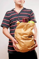 Close_up of a man holding a bag of fruits and vegetables