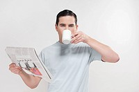 Portrait of a man reading a newspaper and drinking coffee