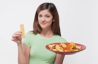 Woman choosing between a protein bar and a platter of nachos