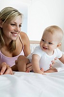 Young mother playing with baby 6_12 months in bedroom