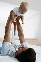 Young father playing with baby 6-12 months in bed, holing up baby (thumbnail)