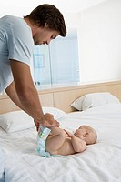 Young father changing babies 6_12 months nappy in bed