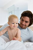 Young father sitting with baby 6_12 months in bed, looking at baby