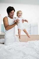 Young father playing with baby 12-24 months in bed, holing up baby, smiling (thumbnail)