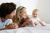 Young parents playing with baby 6_12 months on bed, baby crawling away