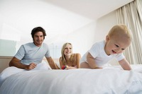 Young parents on bed with baby 6-12 months, baby crawling away (thumbnail)