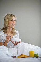Young woman sitting on bed, smiling, eating breakfast