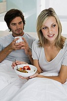 Young couple sitting on bed, smiling, drinking coffee, eating breakfast