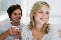Young couple sitting on bed, smiling, drinking coffee (thumbnail)
