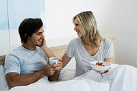 Young couple sitting on bed, smiling, eating breakfast, drinking coffee