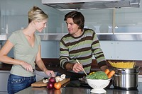 Young couple in modern kitchen, cooking together, smiling, looking at each other