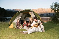 Young Family camping, sitting in front of tent with father playing Guitar (thumbnail)
