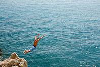 A man dives off a cliff into the sea at Antibes on the Cote D'Azur in southern France