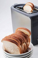 Close_up of white breads in a bowl with a toaster