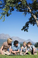 Young Family sitting on grass looking at map, mountains in background, outdoors