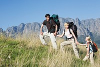 Young couple with daughter hiking with backpack, mountains in background (thumbnail)