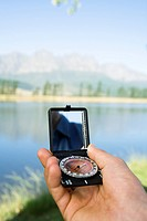 Hand holding compass, outdoors, pointing at landscape, close_up