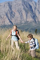 Two children outdoors, hiking with backpack, mountains in background (thumbnail)