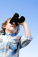 Boy 4-7 standing outdoors using binoculars (thumbnail)