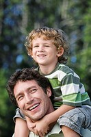 Father carrying son 4-7 on his shoulders, outdoors, forest in background (thumbnail)