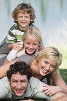 Family with two children lying on grass, human pyramid, in front of lake
