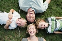 Family with two children lying on grass, looking up, overhead view