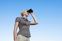 Woman standing outdoors using binoculars