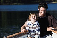 Father and son 4_7 in rowing boat, on lake, laughing