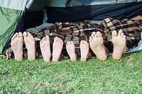 Young Family camping, lying in tent with feet sticking out