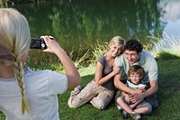Girl photographing family outdoors, family posing for picture