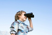 Boy 4_7 standing outdoors using binoculars