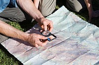 Man holding compass, looking at map, close_up from above