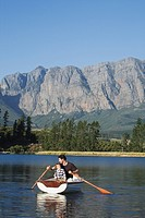 Father and son 4_7 rowing in rowing boat on lake, high mountains in background